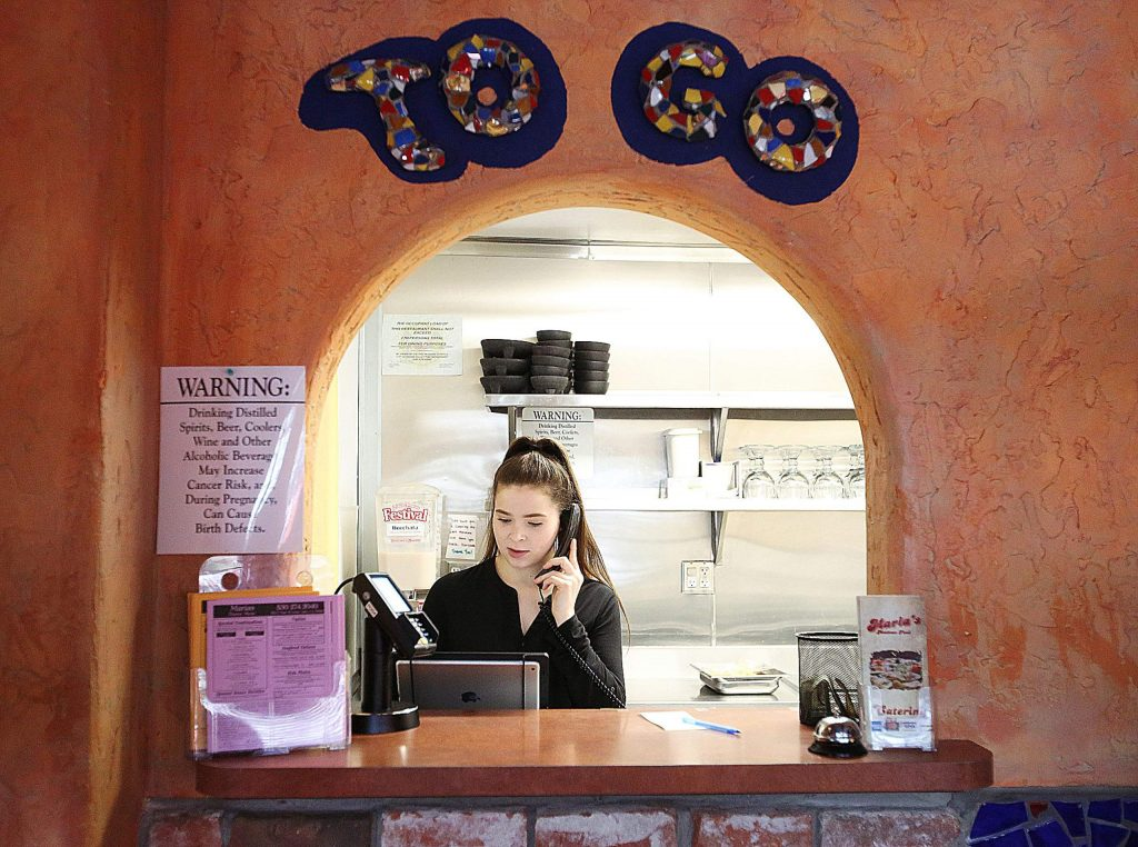 Maria's server Taylor Edmondson takes a to-go order from the takeout window of the downtown Grass Valley restaurant Wednesday afternoon.