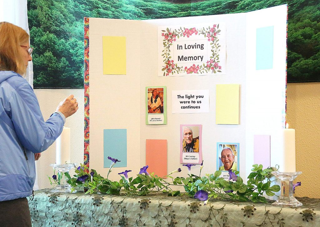 Unity in the Gold Country congregant Kristie Stevens, who put the Wall of Remembrance together, lights a pair of candles near a panel of the wall. People can send photos of deceased loved ones to goldcountryunity@gmail.com for inclusion on the Wall of Remembrance at Unity in the Gold Country.