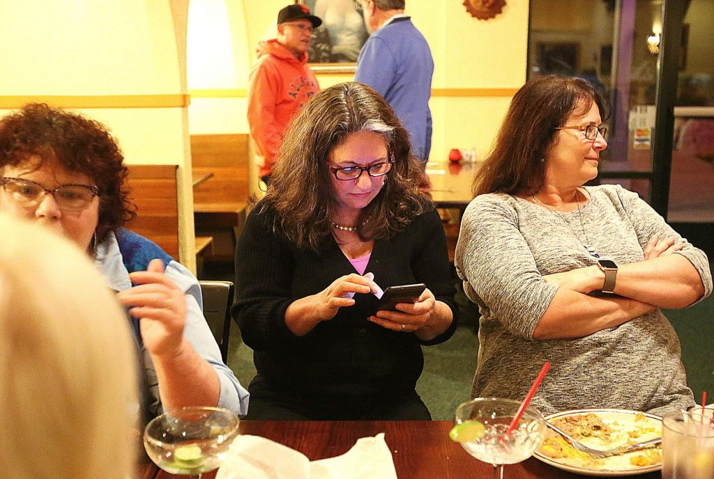Nevada County District 1 Supervisor Heidi Hall checks her cellphone for early election results Tuesday evening at the Margarita's Restaurant election watch party.