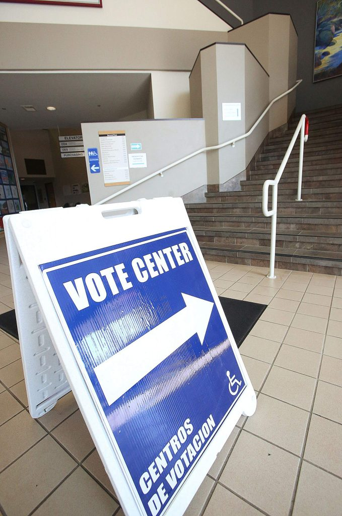 Signs in the lobby of the Eric Rood Administrative Center lead voters to the vote center upstairs.