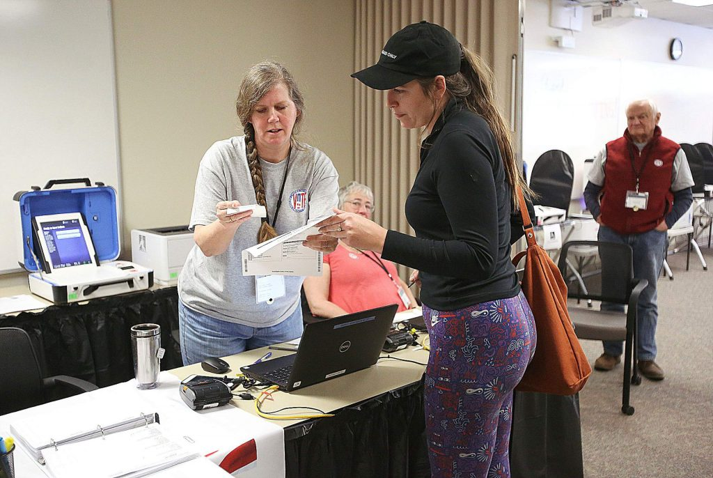 County elections workers help folks with any questions they may have about registering to vote, changing parties, or voting process Saturday at the Nevada City vote center upstairs in the Rood Government Center.