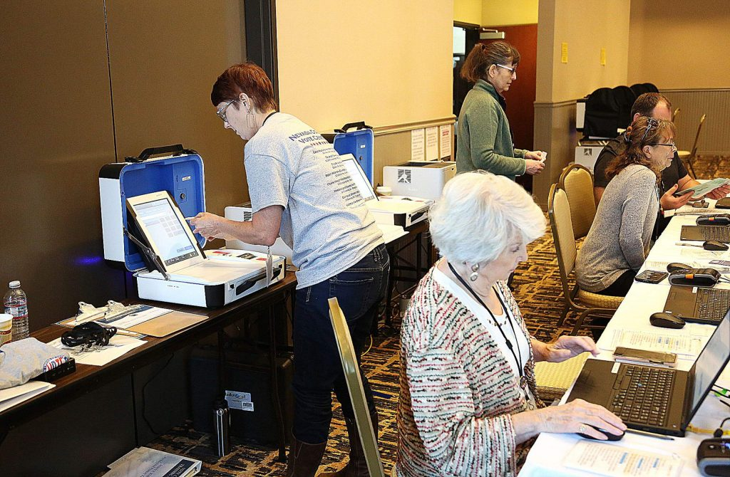 Nevada County elections workers were busy behind the desks Saturday at the Gold Miners Inn vote center.