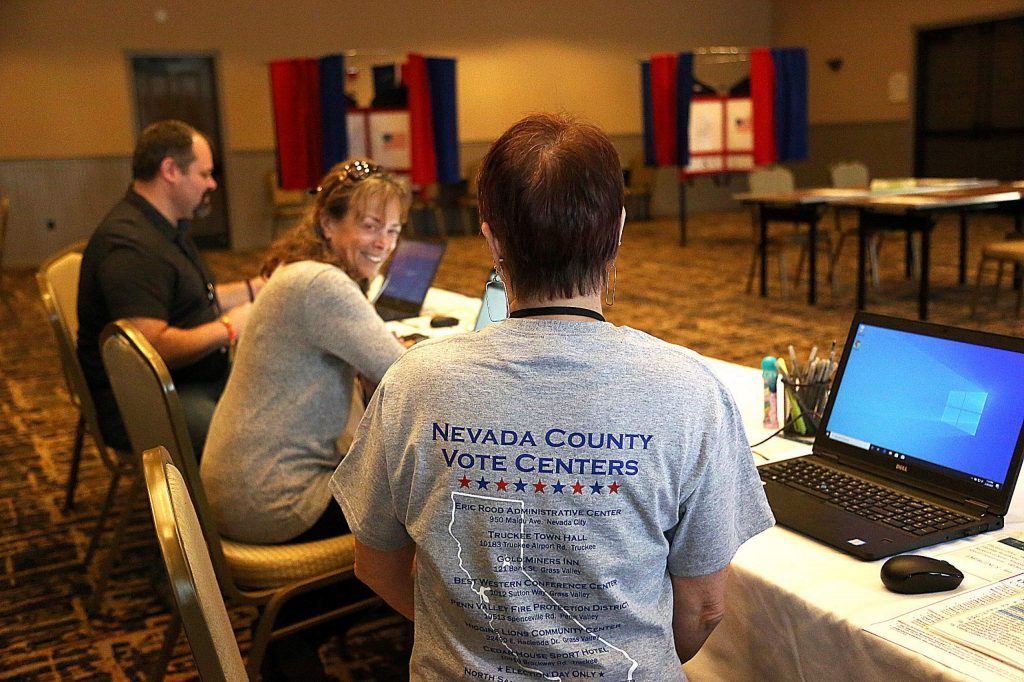 Elections workers show off their shirts that show where the Nevada County vote centers are.
