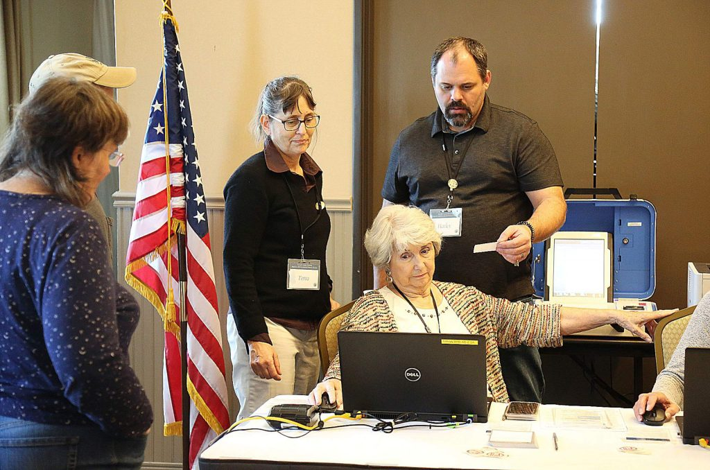 Nevada County elections workers help a voter with a question Saturday at the Gold Miners Inn vote center.