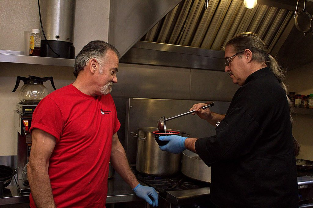 Jeff Giannoni (left) watches as Chef Chris Fagan demonstrates how to ladle soup without splashing. Giannoni's red shirt indicates he is a graduate of Hospitality House Serves, the culinary training program of Hospitality House. He will assist Fagan in making the soups for Empty Bowl 2020.