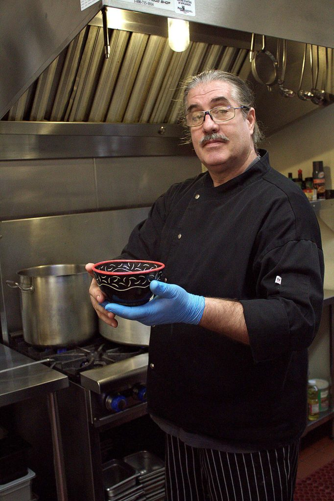 Standing in the state-certified kitchen at Utah's Place, Chef Chris Fagan holds an Empty Bowl from 2014.