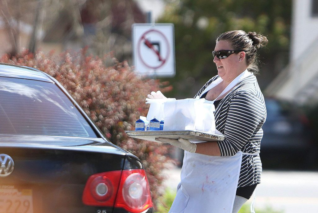 Emily Scott of Emily's Catering and Cakes carries a tray of lunches to a car in front of her storefront off of Colfax Highway in Grass Valley Friday as part of her free lunch Friday program.
