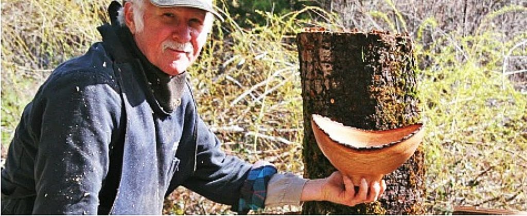 Master woodturner Mike Snegg holds up one of his bowls made with his lathe in his Nevada City workshop.