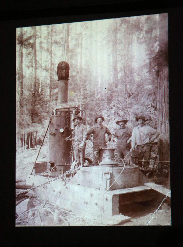 A group of men stand next to a steam donkey in this historical photo. Steam donkeys such as these were instrumental in the construction of flumes for hydraulic mining in the area.