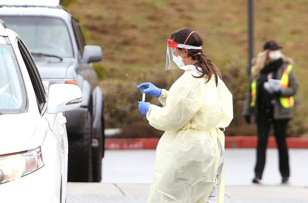 A Sierra Nevada Memorial Hospital nurse in full protective gear places a potential COVID-19 sample into a vial to be tested during Wednesday's drive-thru coronavirus testing outside of the hospital. More than 20 tests were administered Wednesday and will be processed by Quest Diagnostics with results returned in a few days.