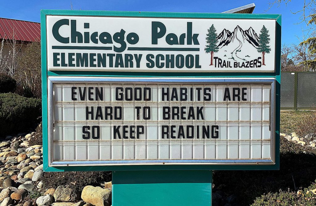 Bob Schmitt, known to Chicago Park Elementary School students as Mr. Maintenance Man, updates the school's marquee with motivational messages to inspire students to read.