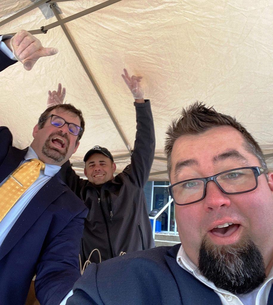 Staffing a tent outside the high school, Nevada Union Vice Principals Tim Reid and Luke Browning, plus Facilities Manager Jordan Kohler, center, take joy in distributing containers with two- to three-days' worth of breakfast and lunch meals.