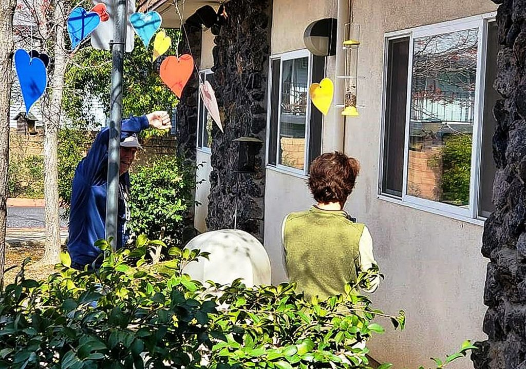 While restricted from entering nursing homes, families and friends visit with loved ones outside patients' windows, such as these visitors at Spring Hill Manor Rehabilitation & Convalescent Hospital. Messages featuring hearts are popular.