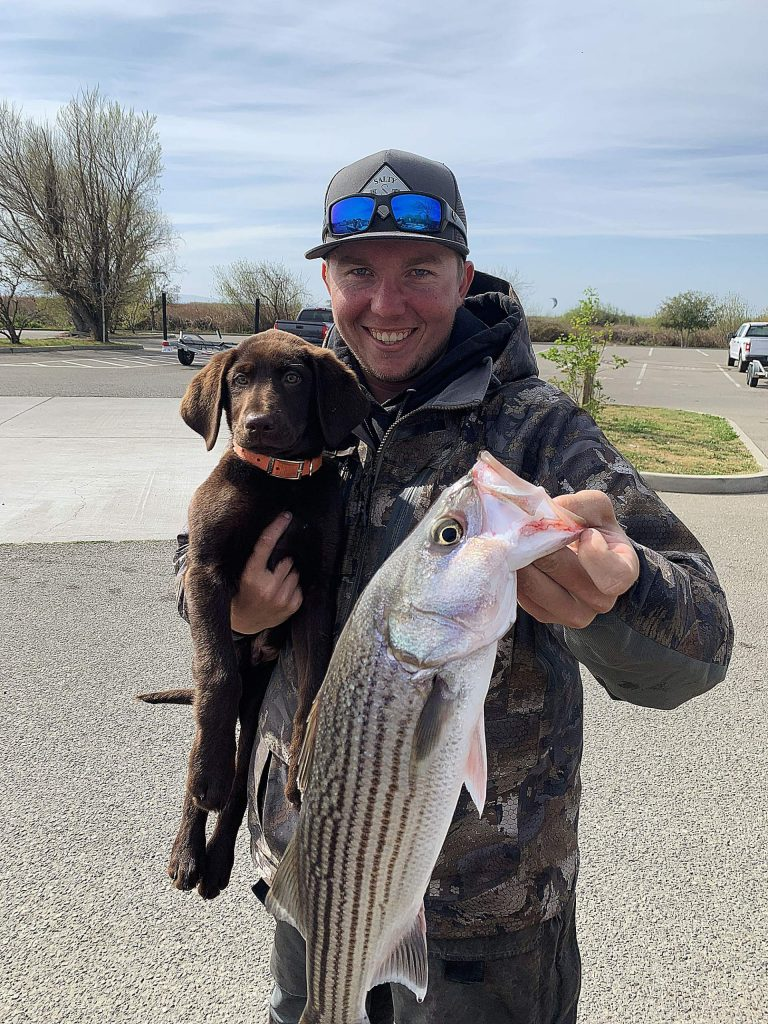 Local guide Justin Leonard with big striper. And puppy.