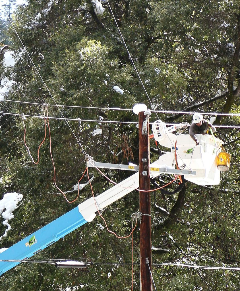 A PG&E line worker works to help restore power to Cascade Shores residents Thursday morning along Pasquale Road.