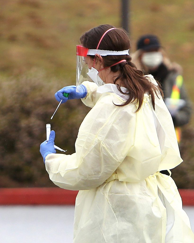 A potential coronavirus swab is placed in a vial to be tested by Quest Diagnostics March 18 at Sierra Nevada Memorial Hospital in Grass Valley where folks participated in drive-thru testing.