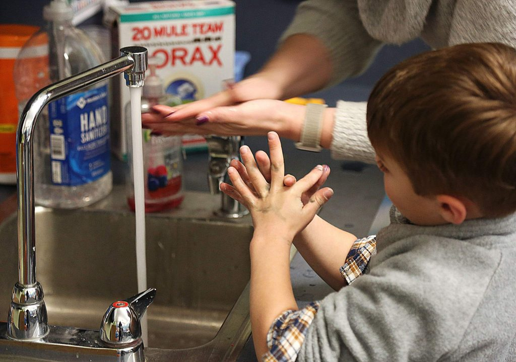 Children are shown proper hand washing procedures at a day care for local health care workers offered by staff at Chicago Park Elementary School.