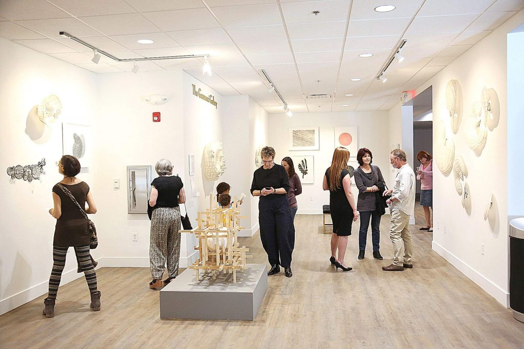 """Folks mingle about the grand opening of the gallery at The Center For the Arts in downtown Grass Valley days before the center closed its doors due to COVID-19 concerns. Artist Nancy Mintz christened the gallery with her show """"Strata"""" adjacent to the center's lobby."""