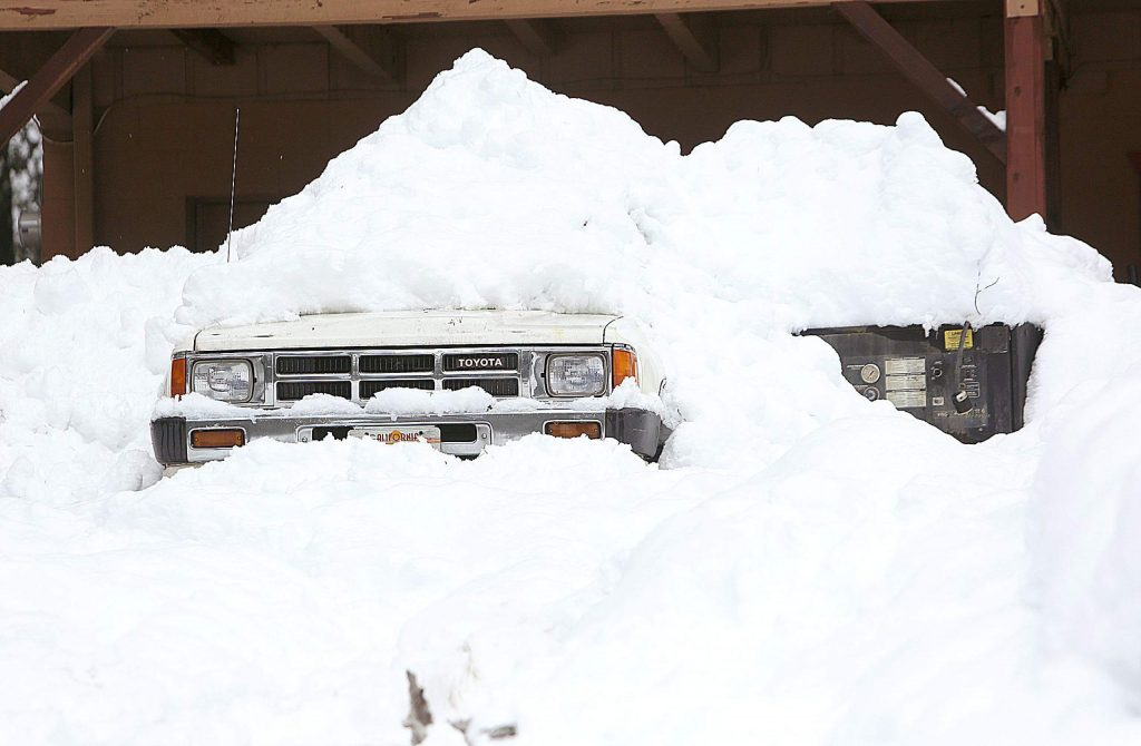 A 1980s Toyota pickup is almost but completely covered in snow in front of this Cascade Shores home.