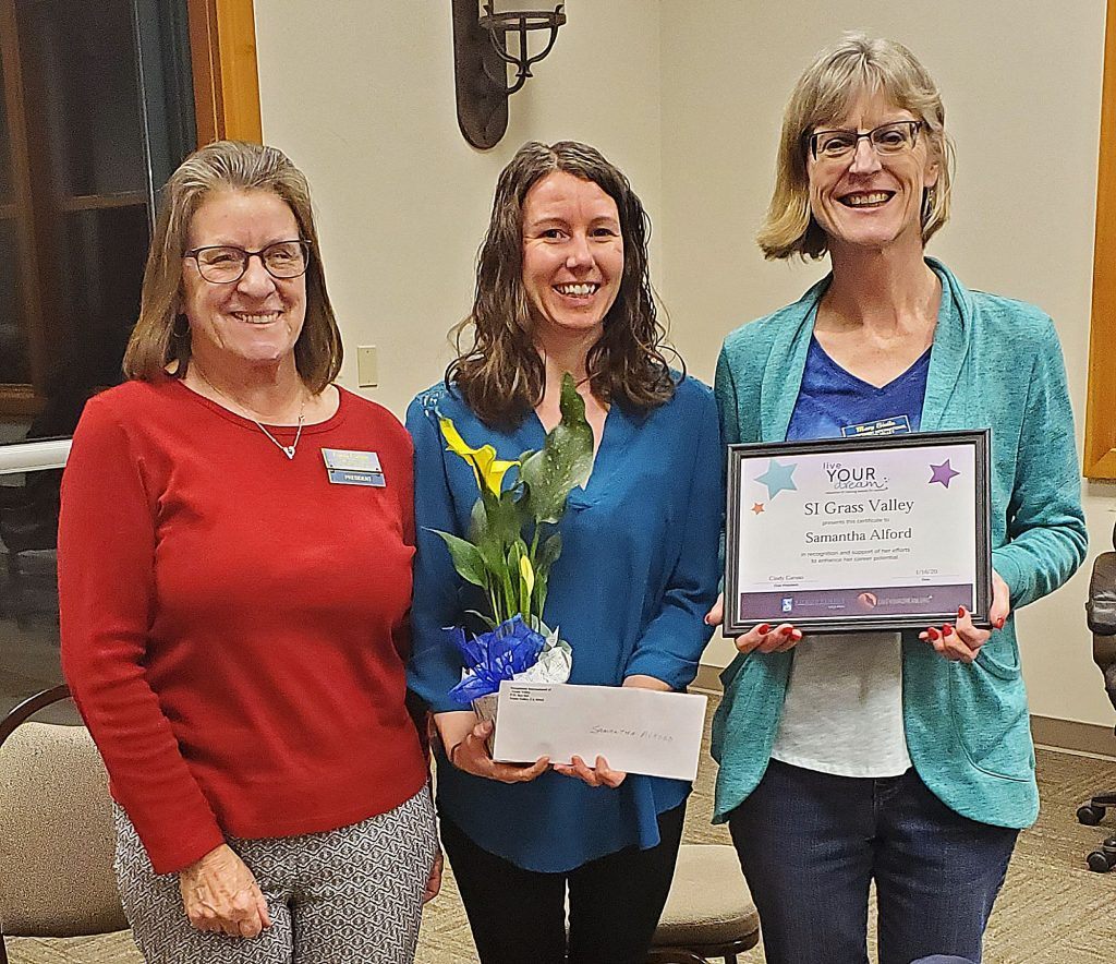 Soroptimist members Cindy Caruso, left, and Mary Sivila, right, present Samantha Alford, center, with a