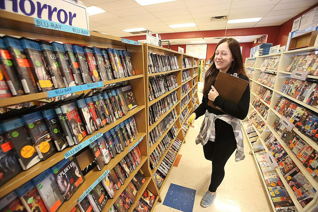 Video Library employee Paris Drake smiles as she checks on the inventory of the store's shelves Friday afternoon.