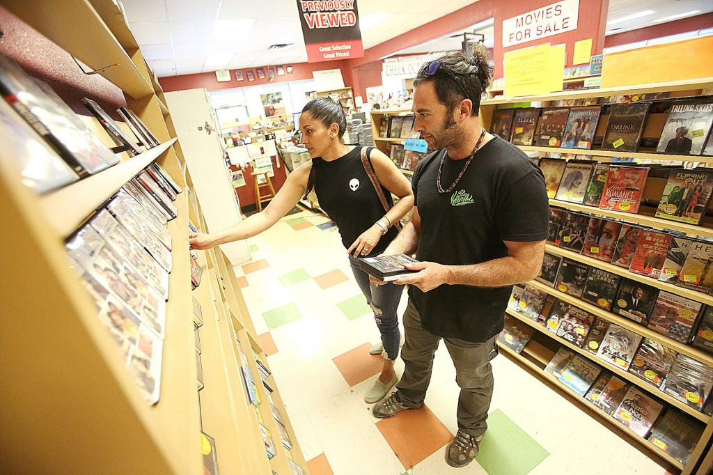 Peter and Deyra look for the perfect movies from the shelf Friday afternoon at Grass Valley's Video Library. After publishing that the store was in the process of closing, interest in purchasing the store and keeping it open has surfaced from interested parties.