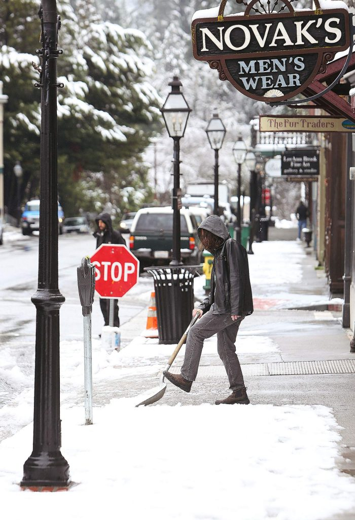 A man removes a few inches of snowfall from in front of the Fur Traders' store along Broad Street in Nevada City Monday morning.