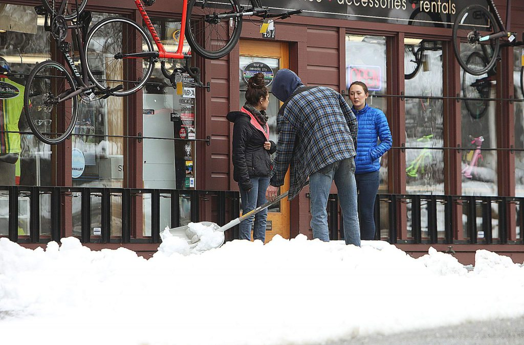 Snow is shoveled away from the front of Tour of Nevada City bicycle shop Monday morning.