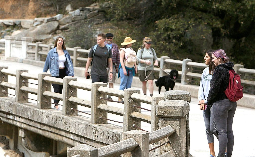 Groups of folks keep their distance from one another as they take to the Highway 49 bridge of the South Yuba River Saturday in the Sierra Nevada.