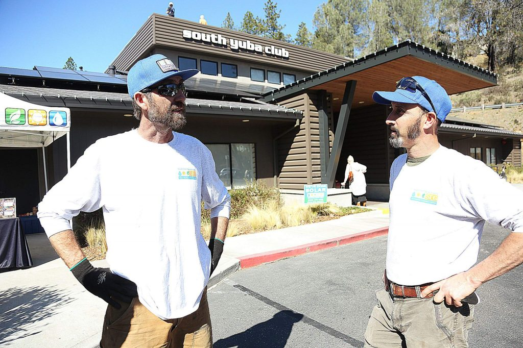 Sustainable Energy Group employees talk about some of the different aspects of the solar array that went online this week at the South Yuba Club gym.