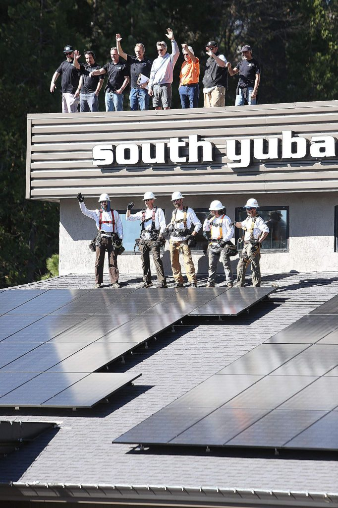 Sustainable Energy Group and South Yuba Club workers celebrate the new solar panel install on the roof of the Grass Valley gym.