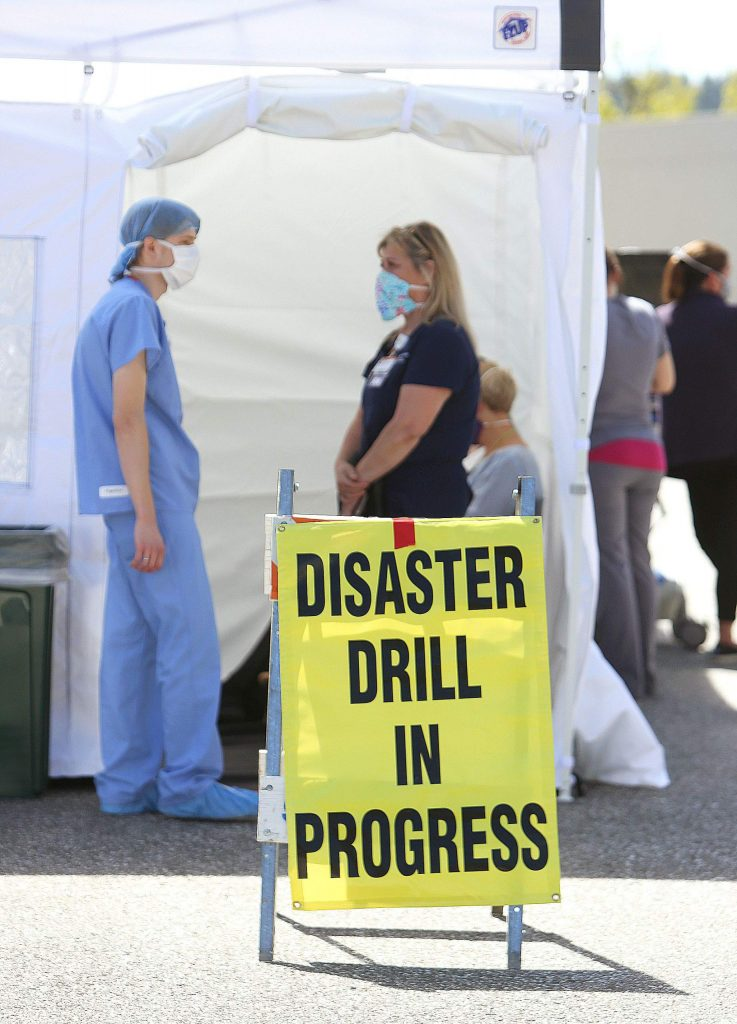 Doctors and nurses work in a series of pop-up tents set up outside of the Sierra Nevada Memorial Hospital emergency room as they would during a triage event.