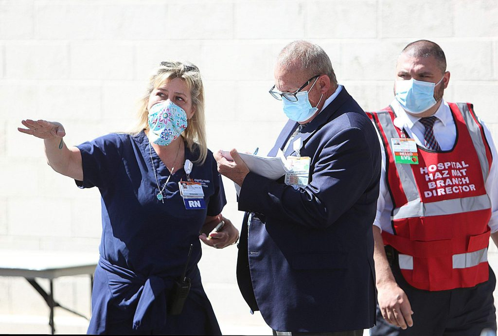 Sierra Nevada Memorial Hospital Chief Medical Officer Jeff Rosenburg takes notes from a nurse involved in Thursday's high surge COVID drill.