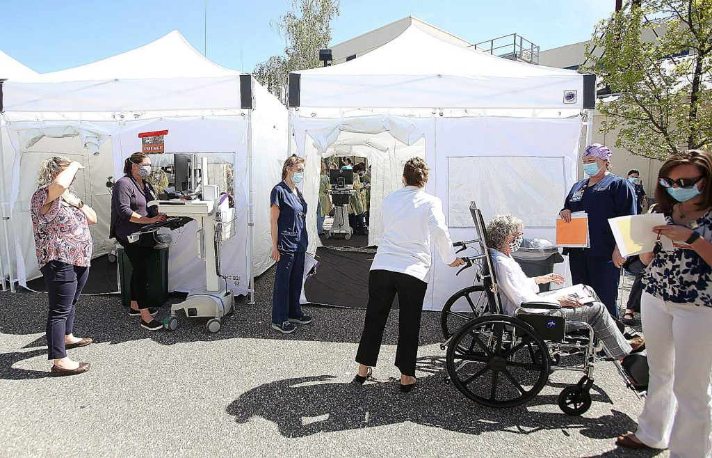 Simulated patients are processed through the emergency triage system set up outside of Sierra Nevada Memorial Hospital's emergency room during Thursday's high surge COVID drill.