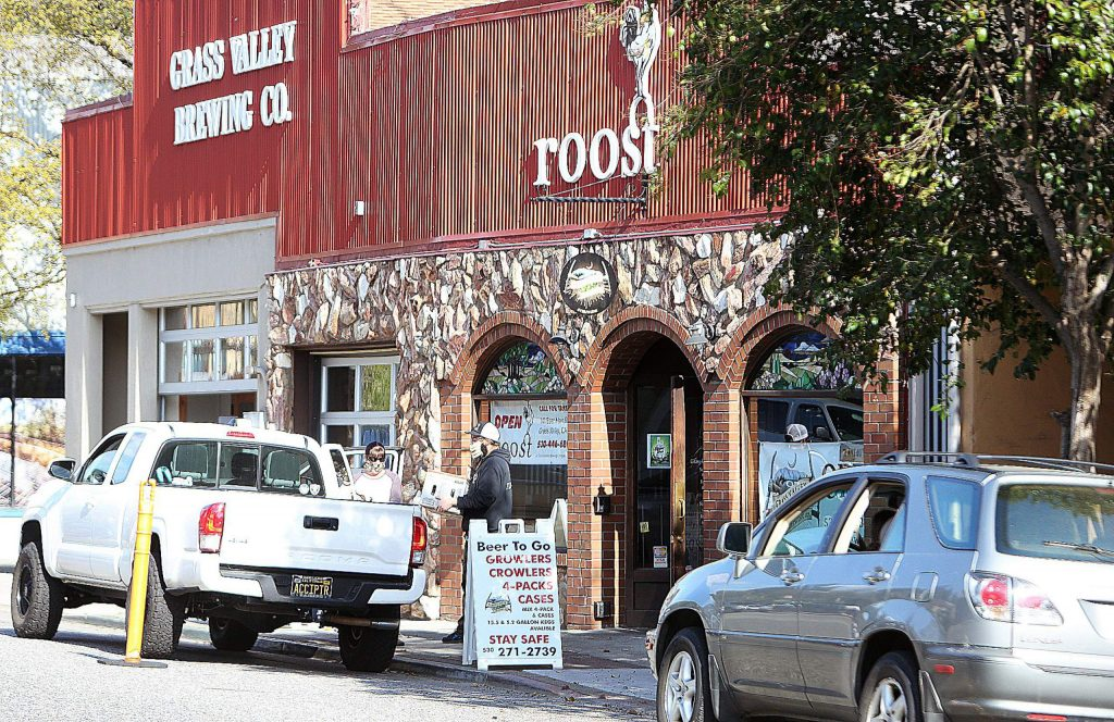 A line of cars awaits a curbside pickup at downtown Grass Valley's Grass Valley Brewing Co.