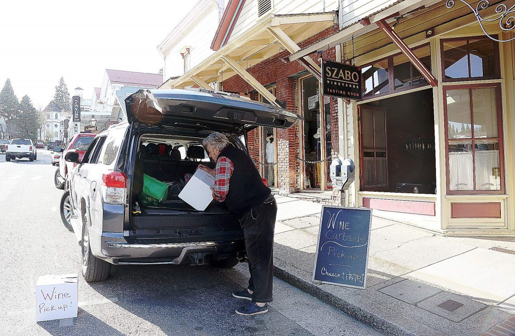 Alex Szabo of Szabo Vineyards places a box of wine in the back of a customer's vehicle Saturday in front of his tasting room off of Broad Street in Nevada City.