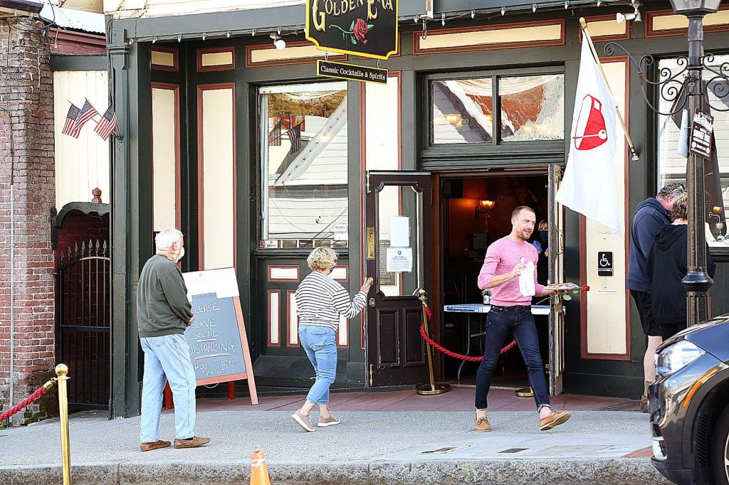 Folks keep socially distant as they place and pick up their curbside to-go orders at The Golden Era Lounge in downtown Nevada City Saturday.