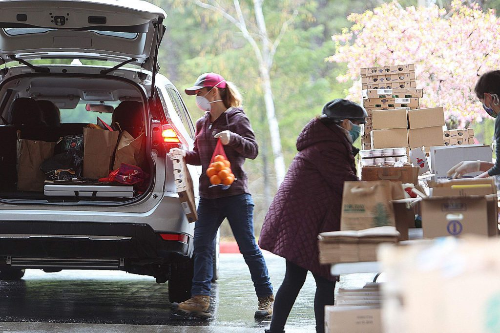 Volunteers wearing gloves and masks help to load vehicles during Thursday's Food Bank of Nevada County drive-thru giveaway at Grass Valley Seventh-day Adventist Church.