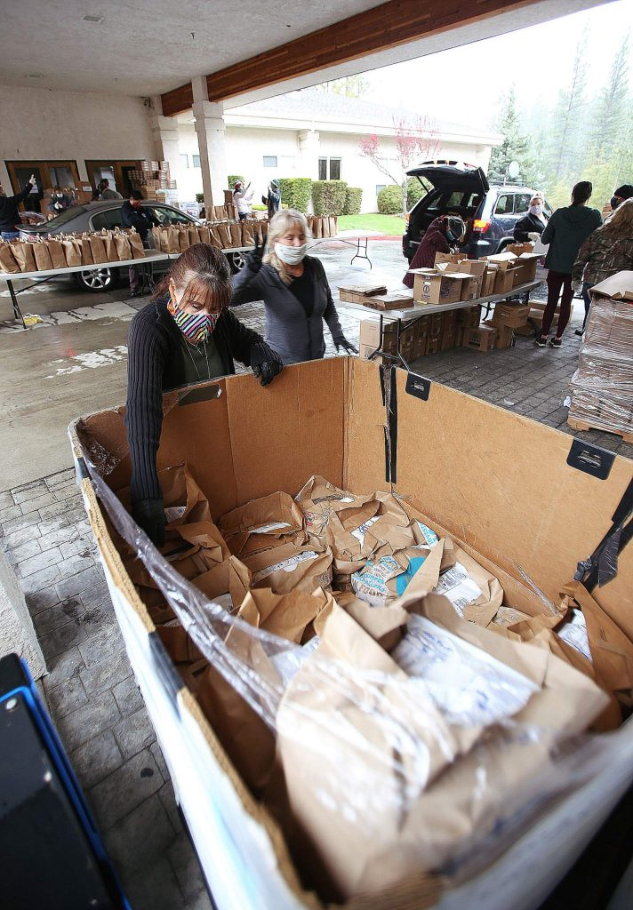 Thousands of pre-packaged bags of food are pulled from pallets and given away during Thursday's Food Bank of Nevada County distribution. Staff are anticipating 1,200 vehicles during next Thursday's giveaway.