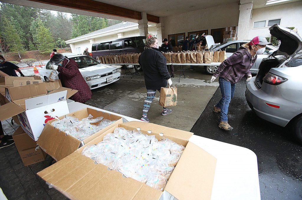 Boxes filled with sliced bags of bread are distributed as vehicles take part in the drive-thru food distribution Thursday at Grass Valley Seventh-day Adventist Church.