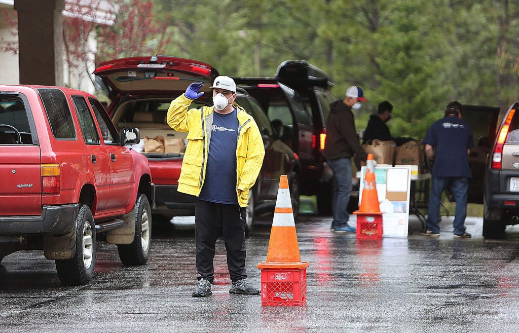 Food Bank of Nevada County general manager Bob Dion helps direct traffic through the drive-thru food distribution last Thursday at the Seventh-day Adventist Church in Grass Valley where over 800 vehicles were served.