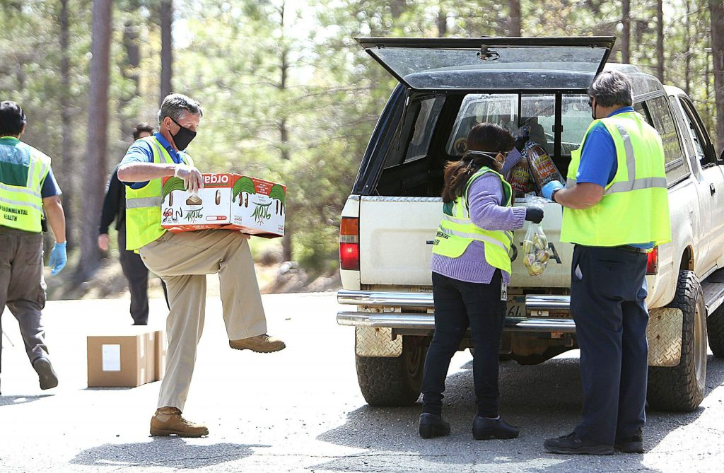 Nevada County disaster service workers help load a vehicle with food Thursday afternoon at the Grizzly Hill School drive-thru distribution site on the San Juan Ridge.