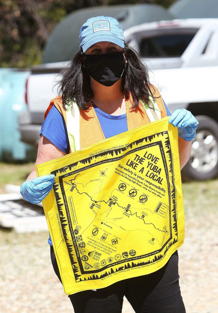 County disaster service worker Stacy Manning holds up one of the bandanas they were giving away Thursday to people without masks or face coverings at the Milhous Feed drive-thru food site on the San Juan Ridge.