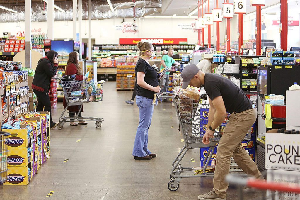 Shoppers heed the 6-foot social distancing mandate while waiting in line at Grocery Outlet in Grass Valley's Glenbrook Basin Wednesday afternoon.