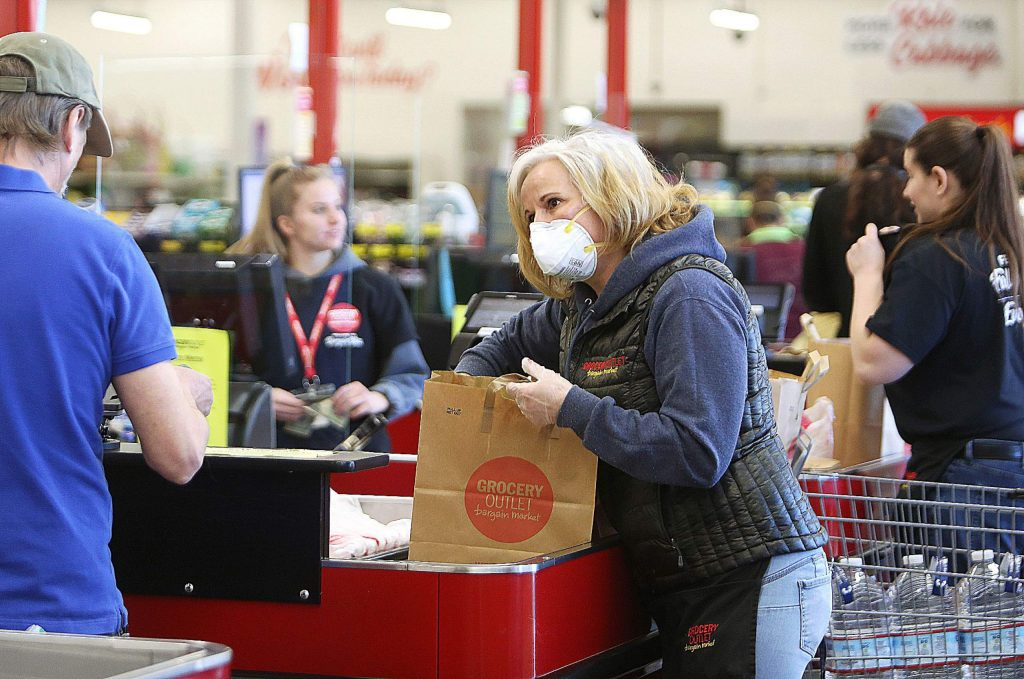 Front lead at Grocery Outlet Kasandra Berry wears an N95 mask while helping bag groceries Wednesday in Grass Valley.