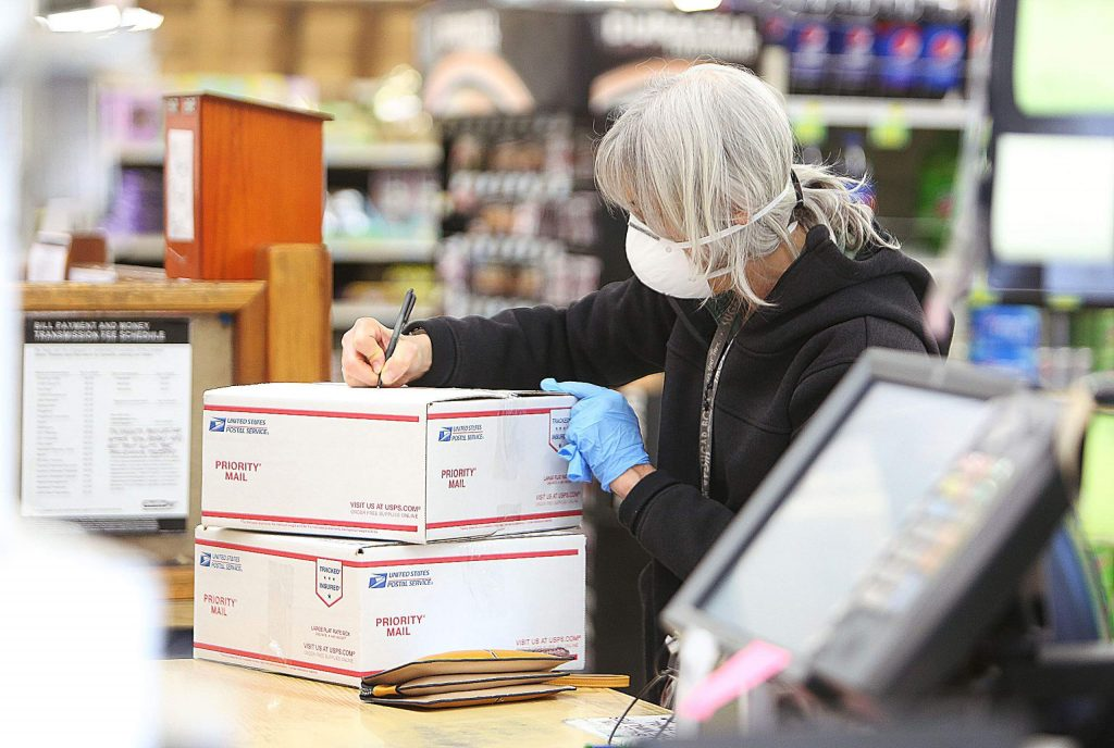 Lisa Mandelbaum wears an N95 mask as she works on mailing a pair of packages Wednesday afternoon at SPD Market in Nevada City.
