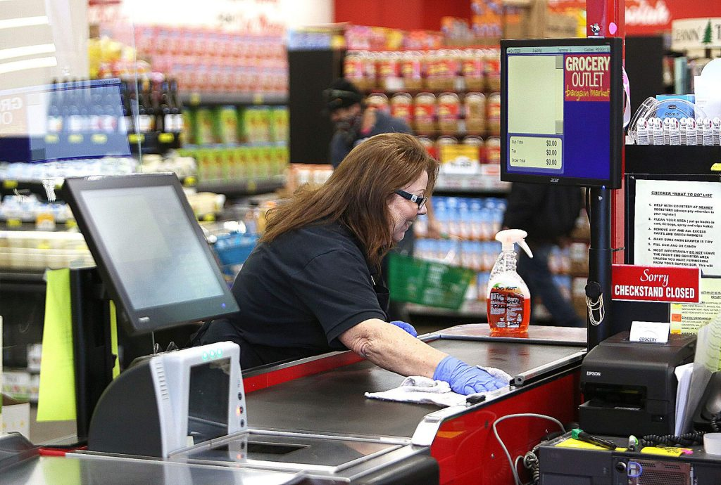 Grocery Outlet workers take time to wipe down surfaces at the checkout aisles Wednesday afternoon in Grass Valley.
