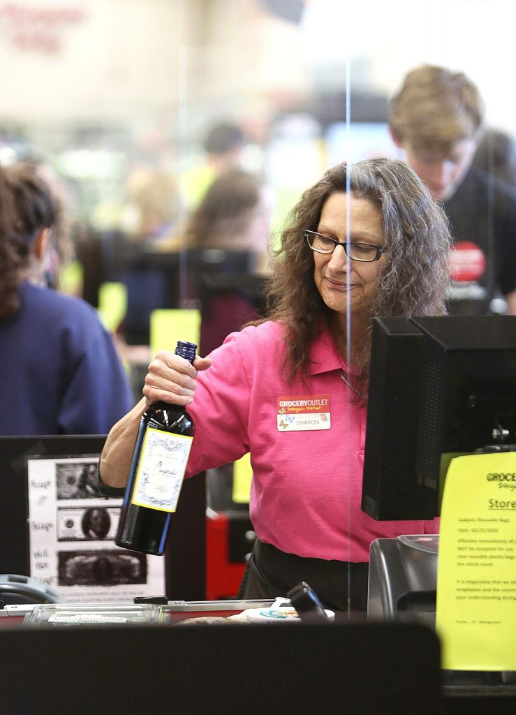 Grass Valley Grocery Outlet checker Sharon Lolli works from behind a plexiglass screen recently installed at checkout aisles to better help protect workers.