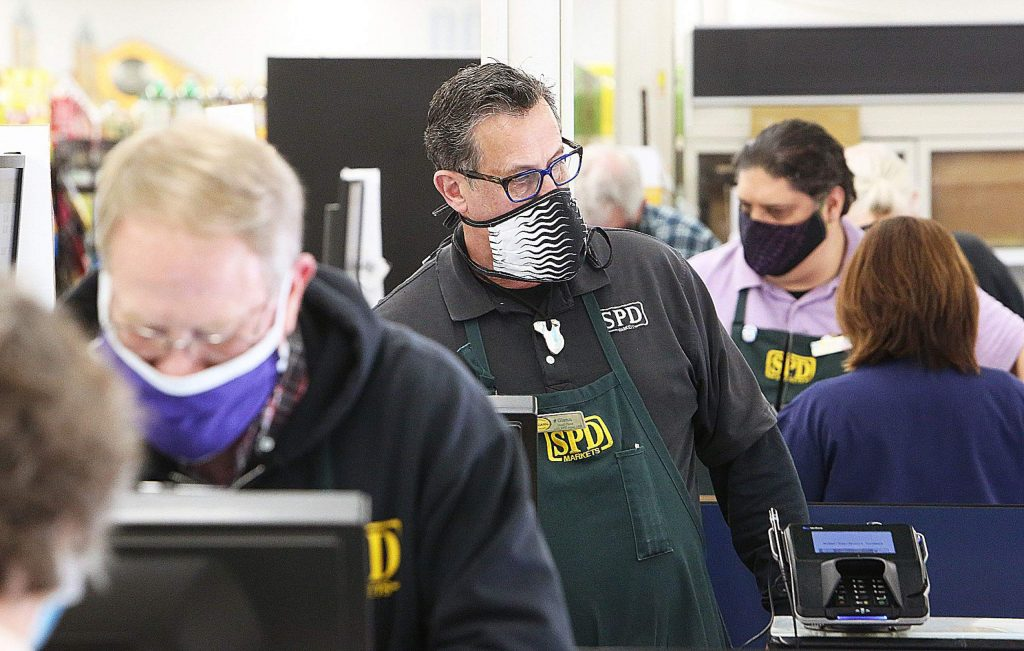 The checkers at SPD in Nevada City all wear masks while ringing up customers for their groceries Tuesday at SPD in Nevada City.