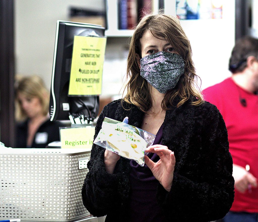 Lexis LaRue shows off a sealed bag of sterile masks that were dropped off by an NC Masks volunteer at B&C Ace Hardware in Grass Valley. LaRue is wearing a custom-fitted mask made by seamstress Gwen Fackrell.